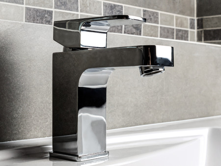 Modern bathroom chrome faucet with white ceramic washbasin Stock Photo