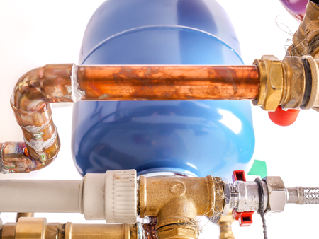 Copper piping system with expansion tanks and pressure gauge in house boiler room