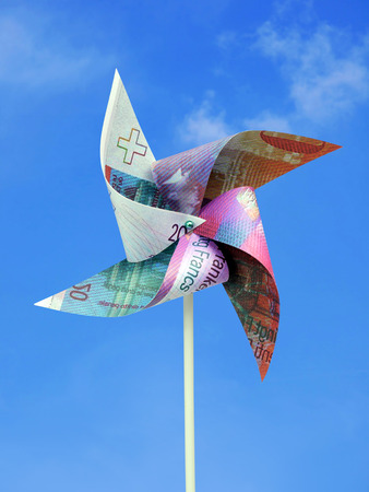 20 Swiss Frank banknote cut into toy windmill shot over blue sky Stock Photo