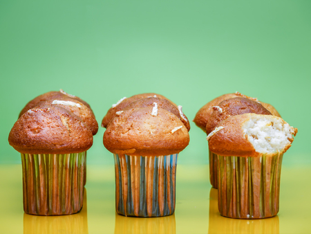 Nine delicious cupcakes, one with bite taken - shot on light green background Stock Photo
