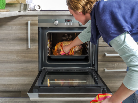 Woman taking out roasted goose from the roaster oven Stock Photo