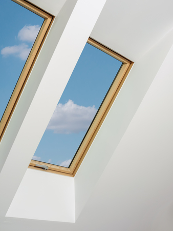 Two attic windows with blue sky view Stock Photo