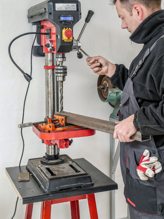 Machinist drilling hole in metal profile