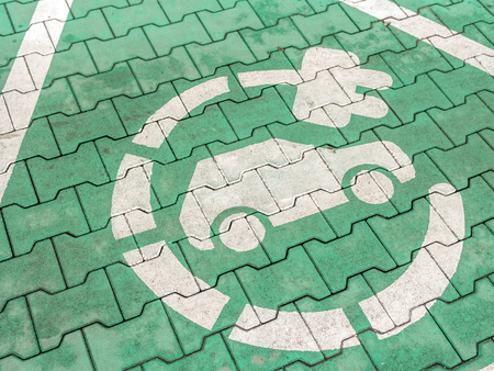 Electric car charging symbol painted on parking lot paving surface Stock Photo