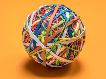 Colorful rubber band ball on orange background