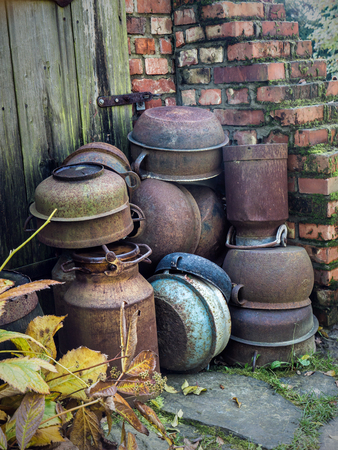 Pile of old farmstead crocks and vessels next to earth cellar Stock Photo