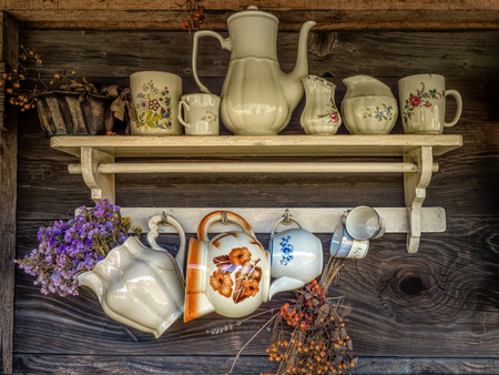 Old wooden rustic shelf with ceramic pots and mugs Stock Photo