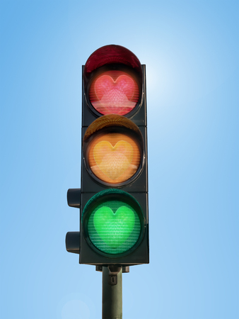 Traffic lights with glowing green, orange and red hearts against blue sky- love concept Stock Photo