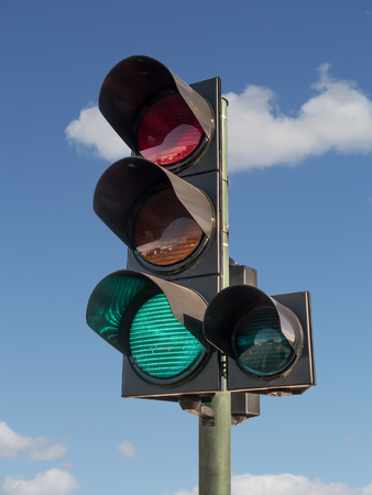 Traffic lights with green light on against blue sky