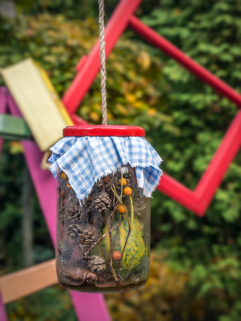 Old glass jar with organic decorations hanging on string in the garden Stock Photo