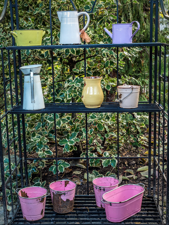 Old watering cans and other garden utensils and vessels placed outside on metal rack as decorations in the garden Stock Photo