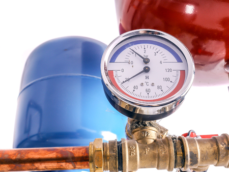 Pressure gauge mounted on copper piping system with expansion tanks in house boiler room