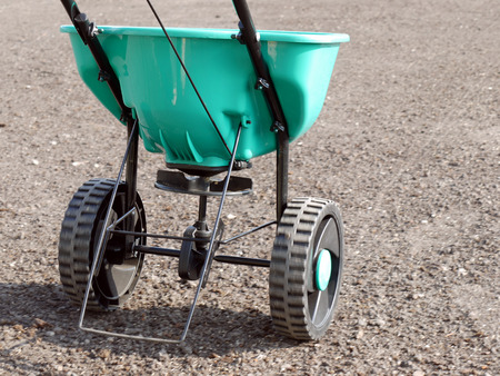 Manually operated seeder filled with grass seeds shot on soil Stockfoto
