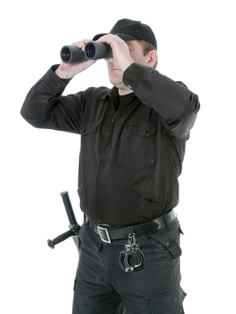 Border guard wearing black uniform looking through binocular, shot on white