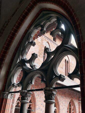 MALBORK, POLAND - 15 AUGUST, 2013: Cloister tracery window of Teutonic Malbork castle, Poland. Malbork castle is the largest brick fortress in the world Redakční