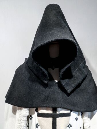 MALBORK, POLAND - 15 AUGUST, 2013: Teutonic order robe with hood  exhibited in the museum in the Teutonic Malbork castle, Poland. Malbork castle is the largest brick fortress in the world
