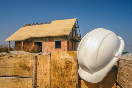 White hard hat affixed to the wooden shuttering wall against the unfinished house
