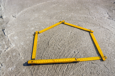 House-shaped yellow wooden folding ruler placed on concrete foundation surface Stockfoto