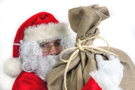 Closeup of Santa Claus with big sack full of christmas presents over white