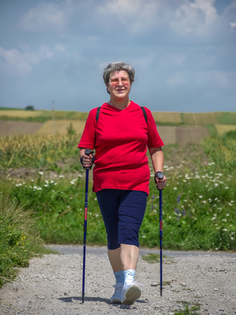 Senior woman practising nordic walking in the countryside