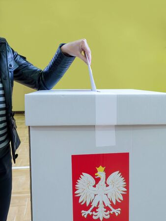 Female voter casting a vote into ballot box during election to the Polish Parliament