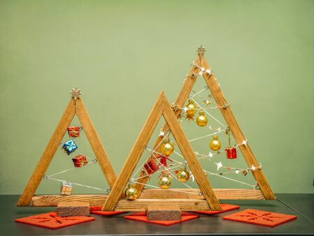 Wooden christmas tree shape decorations against green wall