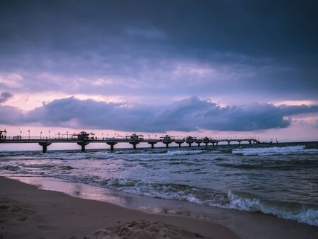 Miedzyzdroje Pier against dramatic sunset sky, The pier is 395 metres long, stretching out into the Baltic Sea from the beach in Miedzyzdroje, West Pomeranian Voivodeship, Poland