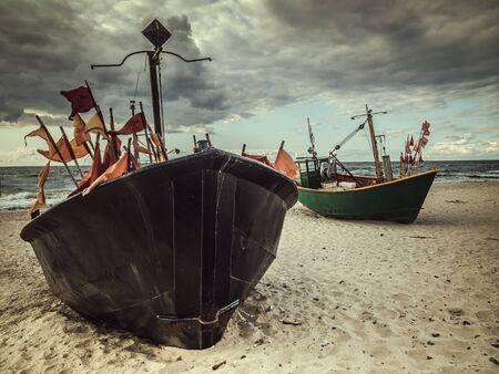 Two fishermans boats docked at the sandy wharf - Miedzyzdroje beach, Poland