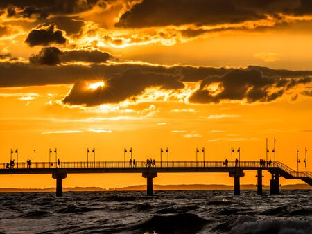 Miedzyzdroje Pier against the setting Sun with tourists silhouettes. Baltic sea, Poland
