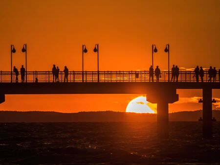 Miedzyzdroje Pier against the sunset sky with tourists silhouettes. Baltic sea, Poland