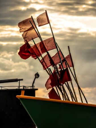 Fishermans boats with fishing flag markers at the sandy wharf