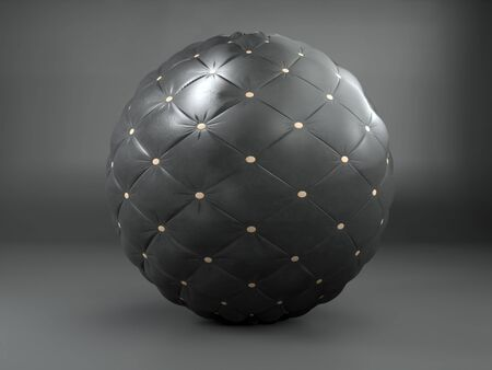 Black leather sphere bradded with golden hobnails on gray background