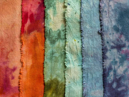 Closeup of overlapping colorful hand-dyed wet cotton fabrics shot from above