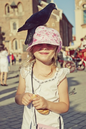 Little girl with pigeon on the head in old town square Stock Photo