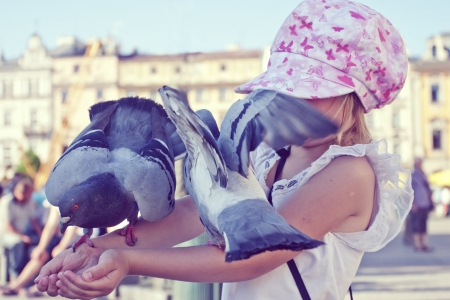 Little girl with pigeons on the arms in old town square