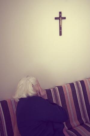 Prayer of grandma sitting on the sofa