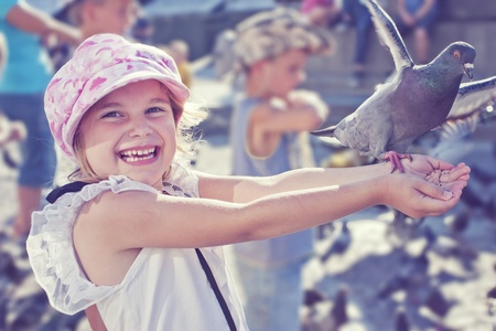 Smiling girl feeding pigeon in old town square