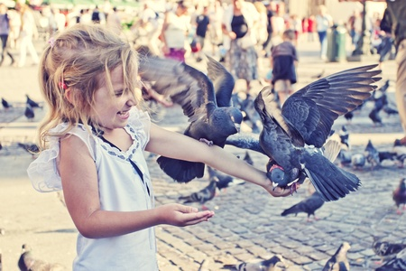 Smiling girl with pigeons on the hand in old town square