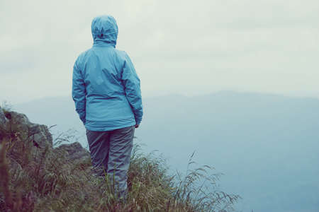 Woman standing over cliff in mountains Stock Photo