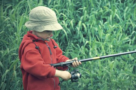 Little boy holding fishing rod  Grass at the background