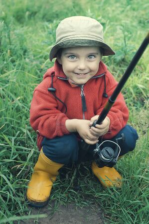 Smiling little boy holding fishing rod  Grass at the background