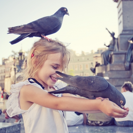 Smiling girl with pigeon on the head and the arms in old town square