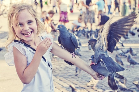10 years old: Smiling girl with pigeons on the arm in old town square