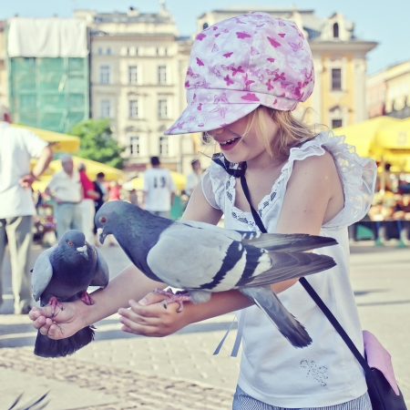 8 10 years: Smiling girl with pigeons on the hands in old town square Stock Photo