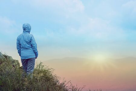 Woman standing over cliff at sunrise Stock Photo