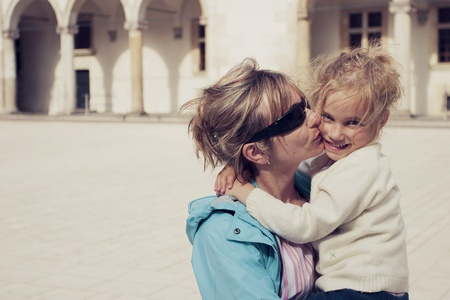 Mom kissing her daughter on the cheek