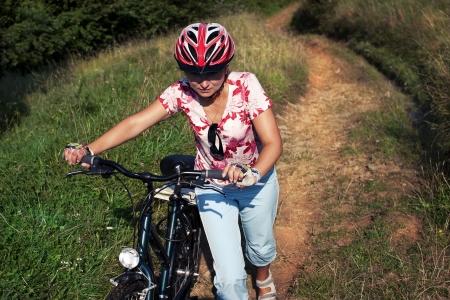 Woman pushing the bike up hill