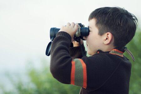 Boy looking through binocular