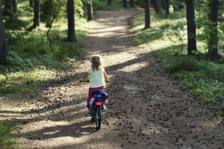 Girl riding a bicycle in the forest Stock Photo