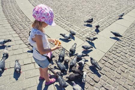 Little girl feeding pigeons on the square